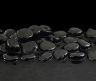 Schwarze Steine auf ruhigem Wasser lizenzfreie stockfotografie