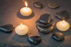 Schwarze Steine und brennende Kerzen auf dunklem Hintergrund Lizenzfreie Stockfotografie