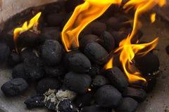 Schwarze Steinkohlenbriketts auf Feuer Lizenzfreie Stockbilder