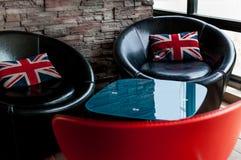 Schwarze Stühle mit Union Jack-Kissen Stockfotos