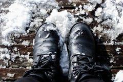Schwarze Stiefel im Schnee mit dem hochauflösenden Treten auf hölzerne Bretter stockfotos