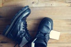Schwarze Stiefel mit Aufkleber etikettieren auf hölzernem Hintergrund Lizenzfreie Stockbilder