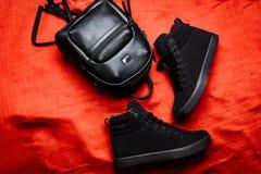 Schwarze Stiefel mit einer flachen Sohle und einem schwarzen ledernen Rucksack auf einem roten Lappenhintergrund stockbild