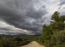 Schwarze Sturmwolken an einem sonnigen Wintertag im Wald und Berge auf der griechischen Insel von Evia, Griechenland stockfotografie