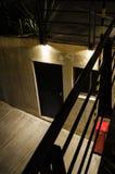 Schwarze Tür auf einer Zementwand und einem roten Kasten auf einer Seite, eine Metallschwarze Geländerdocke im Vordergrund lizenzfreie stockbilder
