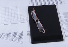 Schwarze Tablette mit den Gläsern, die auf ihr in den Finanzübersichten und in den Diagrammen liegen Lizenzfreies Stockbild