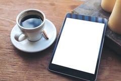 Schwarze Tablette mit weißem leerem Tischplattenschirm und Kaffeetasse, Buch, Kerzen auf Weinleseholztisch im Café Lizenzfreies Stockbild