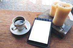 Schwarze Tablette mit weißem leerem Tischplattenschirm und Kaffeetasse, Buch, Kerzen auf Weinleseholztisch im Café Lizenzfreies Stockfoto