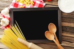 Schwarze Tafel für Menü auf braunem hölzernem Hintergrund Lizenzfreie Stockbilder