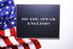 Schwarze Tafel mit der Frage sprechen Sie Englisch? geschrieben in sie und in die Flagge der Vereinigten Staaten von Amerika stockfotografie