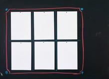 Schwarze Tafel mit sechs leeren weißen Blättern Papier befestigte zu ihr als Mitteilungs-, Rechnungs- oder menuebrett Stockfotografie