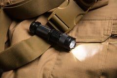 Schwarze Taschenlampe und Schatten auf dem braunen Material lizenzfreie stockfotografie
