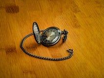 Schwarze Taschenuhr, die auf hölzerner Tabelle stillsteht stockfotografie