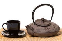 Schwarze Tasse Tee auf Untertassen- und Eisenteekanne auf hölzerner Matte stockfotos