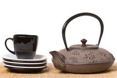 Schwarze Tasse Tee auf verschiedenen Untertassen mit Eisenteekanne auf hölzernem stockbild