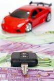 Schwarze Taste, Eurobanknoten und rotes Sportauto Stockfotos