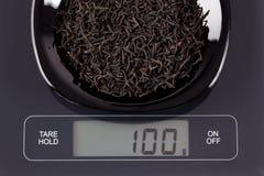 Schwarze Teeblätter auf Küchenskala Stockfotografie