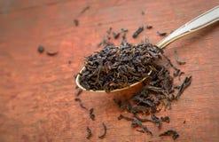 Schwarze Teeblätter in einem Löffel auf einem hölzernen Hintergrund Stockbild