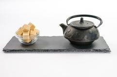 Schwarze Teekanne des Gusseisens und einige Rohrzuckerwürfel im Glasbogen Lizenzfreies Stockfoto
