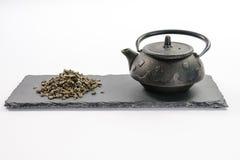 Schwarze Teekanne des Gusseisens und Handvoll grüner Tee des Blattes auf rectangu Lizenzfreie Stockbilder