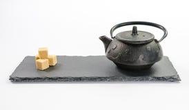 Schwarze Teekanne des Gusseisens und vier Rohrzuckerwürfel auf rechteckigem Lizenzfreies Stockbild