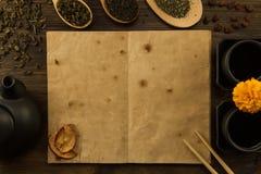 Schwarze Teekanne, zwei Schalen, eine Sammlung Tee, getrocknete Äpfel, altes leeres offenes Buch auf hölzernem Hintergrund Lizenzfreies Stockfoto