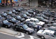 Schwarze Toky-Taxis in den Reihen Stockbild