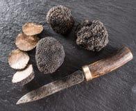 Schwarze Trüffeln und Trüffelscheiben auf einem Graphit verschalen lizenzfreies stockbild