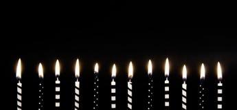 Schwarze u. weiße brennende Kerzen Stockbild