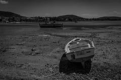 Schwarze u. weiße Fotografie eines Mittelmeerfischerbootes auf dem Strand verursacht durch die Ebbe in Euboea - Nea Artaki, Griec stockfotografie