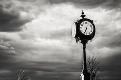 Schwarze Uhr an den Kreuzungen gegen einen stürmischen Himmel Lizenzfreies Stockbild