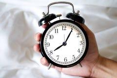 Schwarze Uhr der Weinlese in der Hand des Mannes Stockfotografie