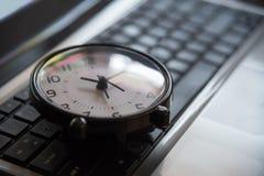 Schwarze Uhr legen auf Tastaturzeit-Metapherkonzept in dunklem niedrigem KE Stockfotos