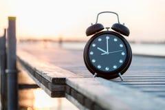 Schwarze Uhr um 10 Uhr auf einer Anlegestelle bei Sonnenuntergang Lizenzfreie Stockfotos