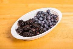 Schwarze und blaue Beeren in der weißen Schüssel auf hölzerner Tabelle Stockfotografie