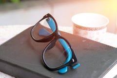 Schwarze und blaue Gläser setzten an das Buch mit Teeschale auf dem Tisch morgens lizenzfreies stockfoto