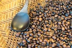 Schwarze und braune Kaffeebohnen in der Bambuswanne mit hölzernem Löffel Lizenzfreie Stockfotografie