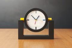 Schwarze und gelbe Uhr auf einem Holztisch Abbildung 3D Stockbild