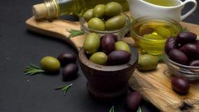 Schwarze und grüne Oliven und Öl auf hölzernem Schneidebrett stock video