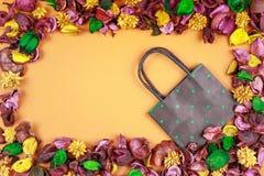 Schwarze und grüne Tupfenpapiereinkaufstasche umgeben durch bunten Trockenblume- und Blattrahmen Draufsicht, flache Lage Stockbild