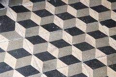 Schwarze und graue Mosaikfliesen ausgebreitet in einem geometrischen Würfelmuster Lizenzfreie Stockfotografie