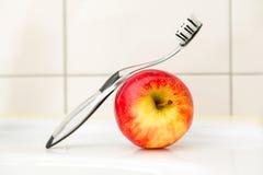 Schwarze und transparente Zahnbürste mit einem Apfel Stockbilder