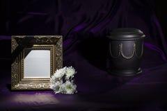 Schwarze Urne mit goldener Dekoration, weiße Chrysantheme, leerer goldener Bilderrahmen auf tiefpurpurnem Hintergrund lizenzfreie stockfotografie