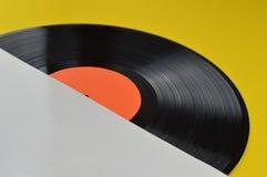 Schwarze Vinylaufzeichnung in der Mitte aus weißer Abdeckung heraus stockbilder