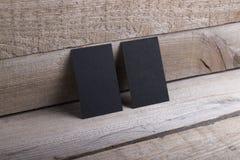 Schwarze Visitenkarten auf altem hölzernem Hintergrund Lizenzfreies Stockfoto