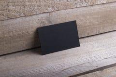 Schwarze Visitenkarten auf altem hölzernem Hintergrund Stockbilder