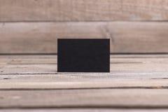 Schwarze Visitenkarten lokalisiert auf altem hölzernem Hintergrund Lizenzfreies Stockbild