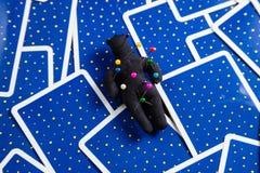Schwarze Voodoopuppe auf einem Hintergrund der tarot Karten. Stockbilder