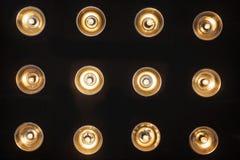 Schwarze Wand mit zwölf eingeschlossenen glühenden Scheinwerfern Stockfotos