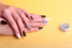 Schwarze, weiße Nagelkunstmaniküre Feiertagsart helle Maniküre mit Scheinen Flasche Nagellack Schönheitshände stockbilder